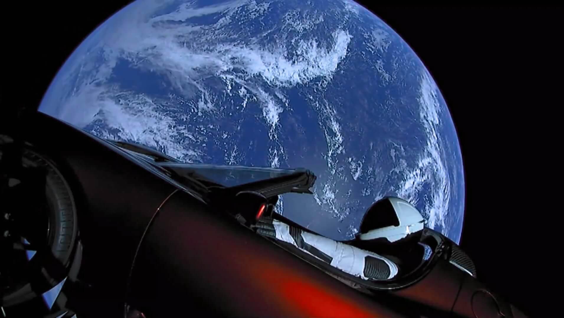 Электрокар Tesla Roadster с манекеном в скафандре на водительском сиденье в космосе