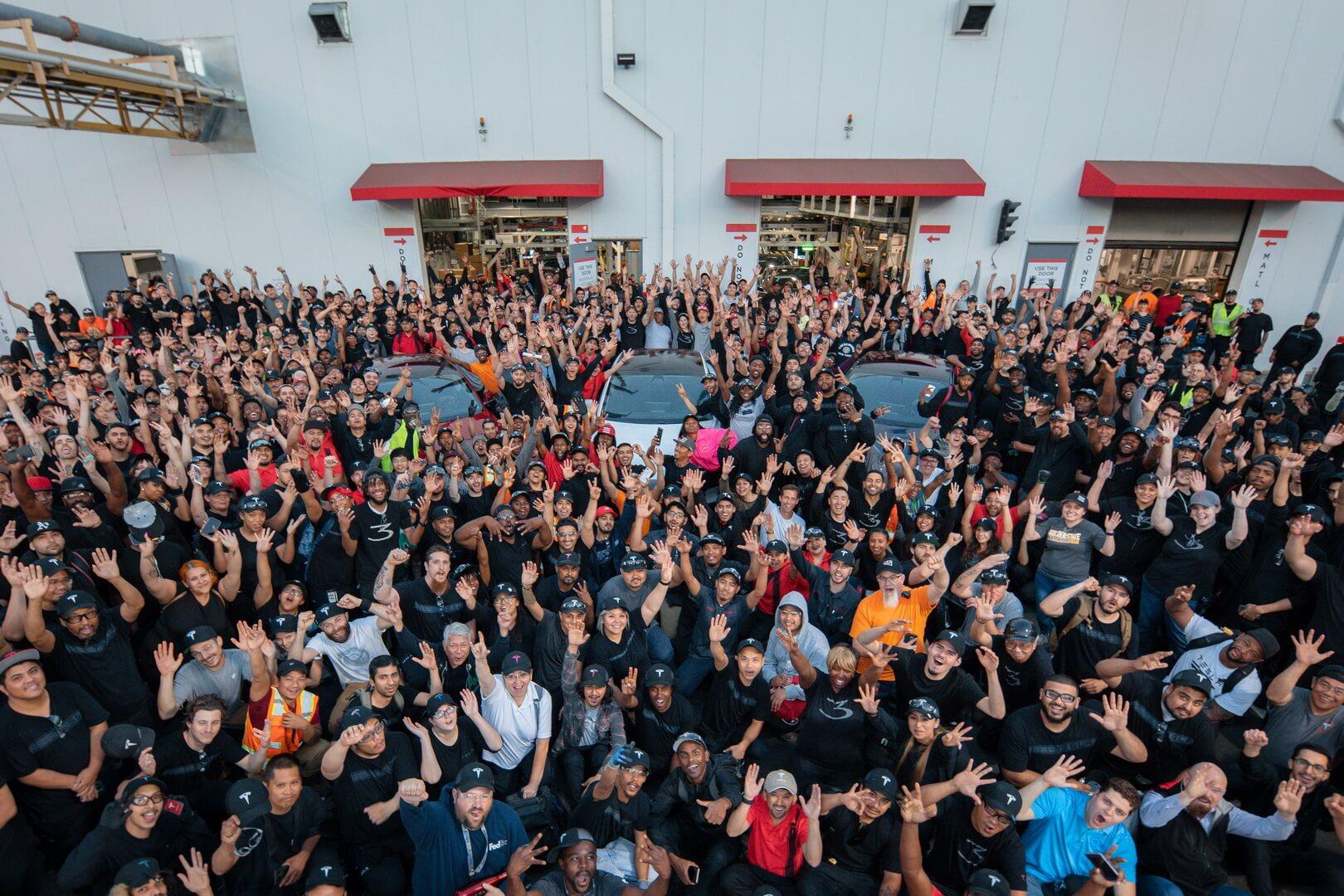 Фотография команды, празднующих достижения целей производства электромобилей Tesla